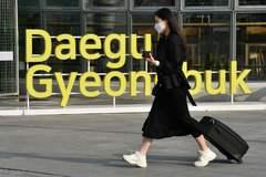 Una mujer con mascarilla protectora camina junto a la estación de tren de Daegu (Corea del Sur).