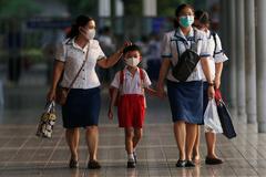Un niño y personal de una escuela abandonan las instalaciones después de que el Gobierno tailandés haya decretado su cierre por el contagio de un niño de 8 años en Bangkok.