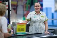 Una cajera de supermercado atiende a los clientes.