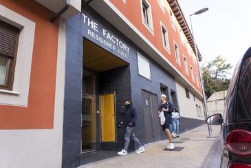 Dos chicos entran en The Factory, la residencia del IE en Segovia a la que un estudiante italiano ha 'importado' el coronavirus, y cuyos 150 moradores están en observación.