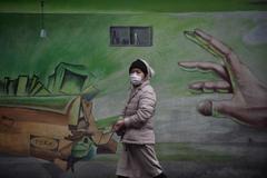 Una mujer camina por las calles de Wuhan.