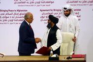 El enviado estadounidense, Zalmay Khalilzad, estrecha la mano al líder talibán Mulá Baradar.