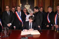 Puigdemont firma en el libro de honor del Ayuntamiento de Perpiñán.