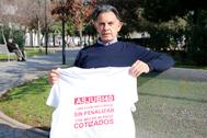 Domingo Laorden muestra una camiseta de su asociación mientras un pensionista toma al sol en  un parque.