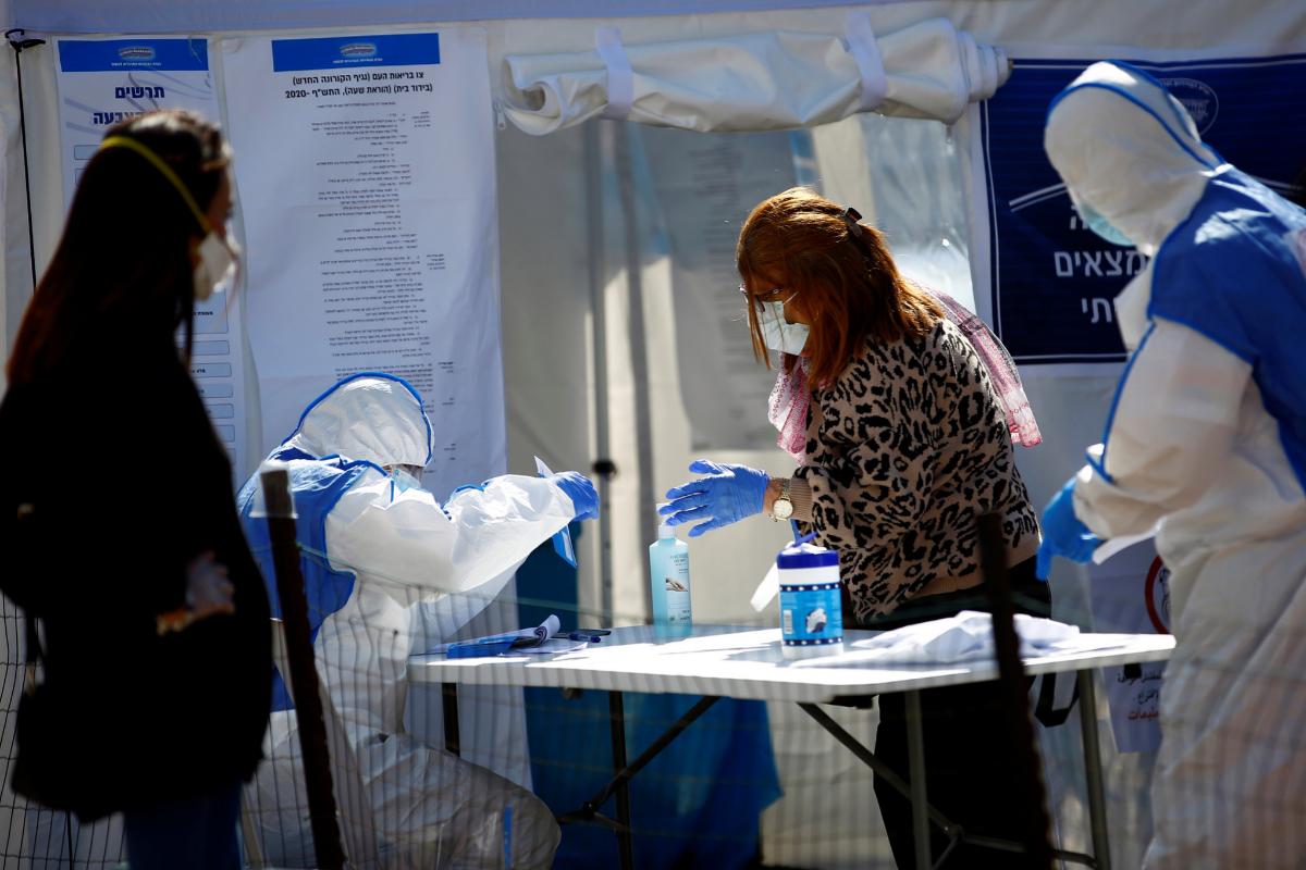 Paramédicos ayudan a votar a una mujer en un centro especial para israelíes en cuarentena por coronavirus.