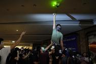 Un manifestante inutiliza una cámara de seguridad en Hong Kong.