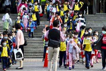 Un grupo de escolares salen de su escuela primaria al final del día en el distrito de Xindian, en Taipei