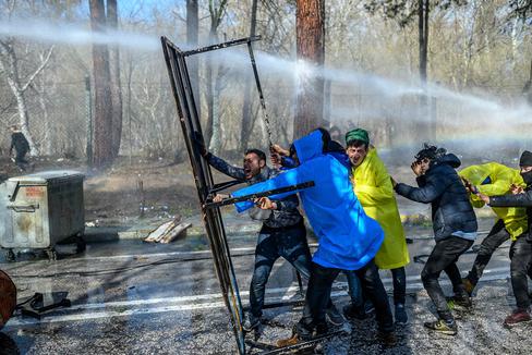 Migrantes se protegen de los cañones de agua empleados por los agentes griegos, ayer, en Edirne.