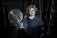 Lourdes López, sosteniendo una radial en su nave de carpintería metálica.