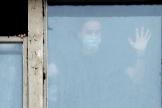 Un estudiante con una mascarillaa sanitaria se asoma a la ventana en un edificio en cuarentena, en San Petersburgo.