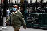 Un hombre con mascarilla frente a una estación de metro de Nueva York.