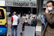 Varias personas con mascarilla ante un hospital madrileño.
