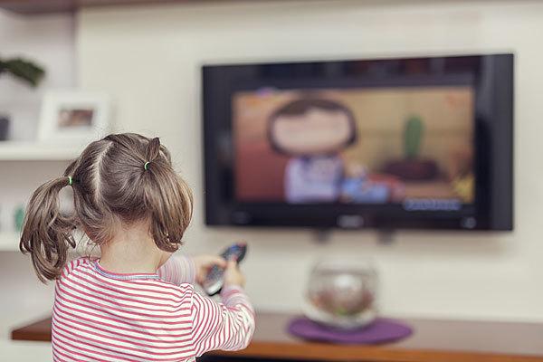 Una niña viendo la televisión.