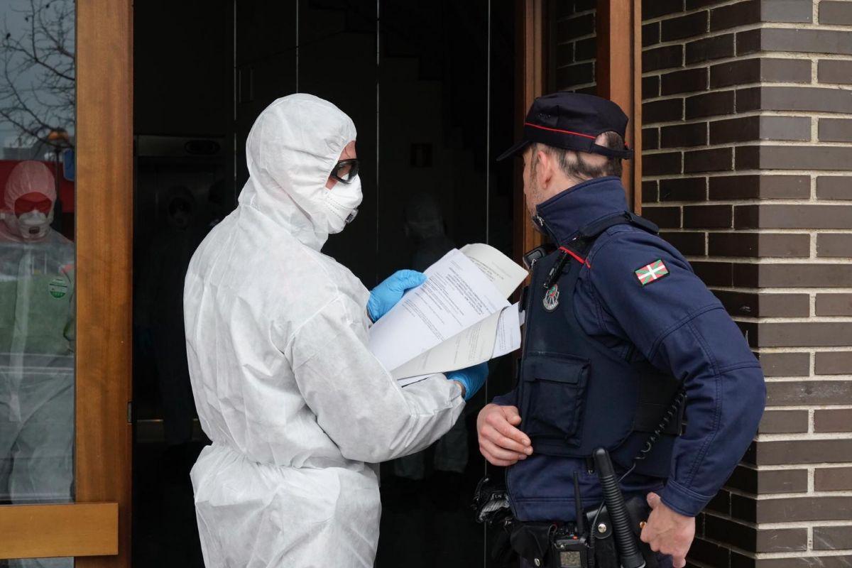 Protegidos contra el virus, agentes de la Ertzaintza notifican a los contagiados por el Covid 19 la prohibición de salir de sus domicilios.