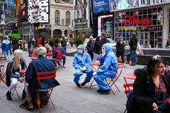 Dos personas con equipos de protección se graban en Times Square (Nueva York)