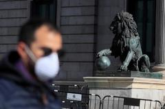 Un hombre con mascarilla pasa frente al Congreso de los Diputados.