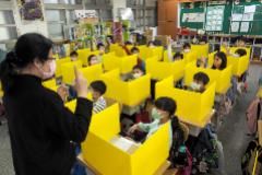Estudiantes protegidos con mascarilla y con tableros sobre los pupitres, asisten a clase en Taipei.