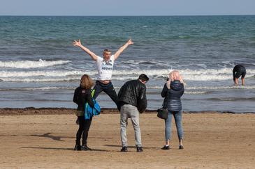 Un grupo de personas se hace fotografías festivas, este viernes, en la playa de la Malvarrosa de Valencia.