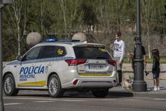 Policías municipales hablando con varias personas que caminaban por el Puente de Segovia, junto a Madrid Río, durante la mañana del domingo.