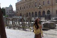 Un turista pasa delante de los palcos a medio montar en la Plaza de San Francisco, en el centro de Sevilla.