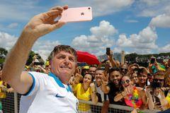 Jair Bolsonaro se hace un 'selfie' con sus seguidores en el Palacio de Planalto.