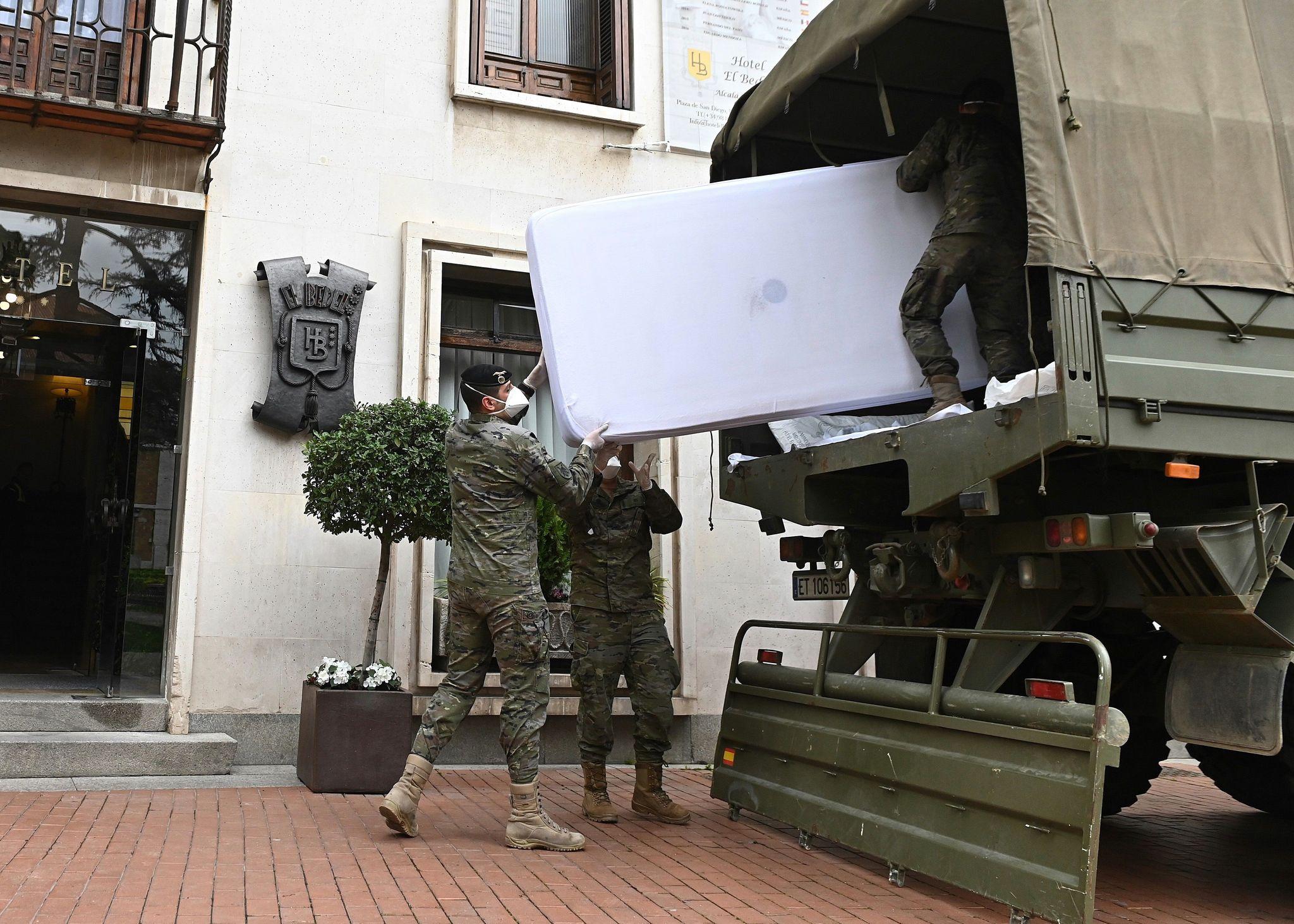 Soldados dela Bripac cargan colchones de un hotel de Alcalá de Henares.