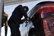 Una mujer echa combustible a su vehículo en una gasolinera de Madrid.