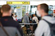 Turistas extranjeros con mascarillas haciendo cola en el aeropuerto de Alicante para facturar el equipaje, este lunes.
