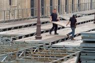 Dos operarios desmontan los palcos de Semana Santa en Sevilla.