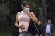 Una mujer embarazada pasea con mascarilla por Bogotá (Colombia).