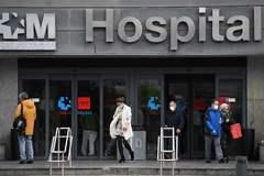 Varias personas con mascarillas a las puertas del Hospital La Paz.