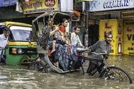 Un grupo de personas logra trasladarse en un 'rickshaw' pese a la inundación causada por una lluvia monzónica en la ciudad de Varanasi, India.