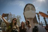 Tres jóvenes se hacen un 'selfie' ante la figura principal de la falla municipal.
