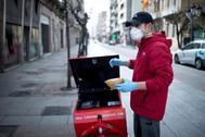 Un repartidor entrega paquetes protegido con una mascarilla