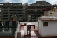 Una pareja pasea por la terraza de un edificio bajo la lluvia durante la cuarentena por coronavirus