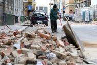 Un hombre limpia una calle de Zagreb poco después del terremoto.
