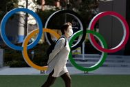 FILE PHOTO: A woman wearing a protective face mask, following an outbreak of the coronavirus disease (COVID-19), walks past the Olympic rings in front of the Japan lt;HIT gt;Olympics lt;/HIT gt; Museum in Tokyo