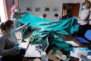 Las mujeres de Benetússer cortando sábanas para mascarillas.