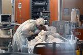 Un médico con un traje de protección habla a un paciente, en un hospital de Roma.