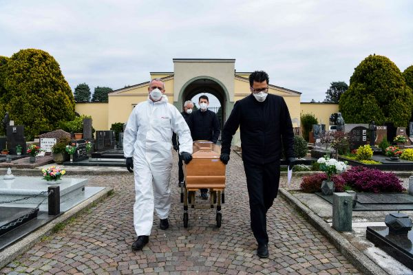 TOPSHOT - Pallbearers pull the lt;HIT gt;coffin lt;/HIT gt; of a deceased person for a funeral ceremony into the cemetery of Grassobbio, Lombardy, on March 23, 2020, in the absence of quarantined relatives. (Photo by Piero CRUCIATTI / AFP)