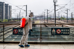 Un trabajador desinfecta la estación de tren de Wuhan.