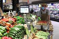Un empleado con mascarilla y guantes en un supermercado