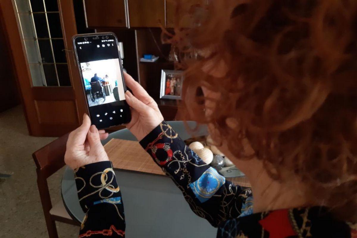 Juani repasa las fotografías de su madre y su hermano en el móvil.