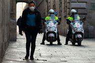 GRAFCAT3176. lt;HIT gt;BARCELONA lt;/HIT gt;.- Una persona camina por una calle del centro histórico de lt;HIT gt;Barcelona lt;/HIT gt; junto a una patrulla de los lt;HIT gt;Mossos lt;/HIT gt; d'Esquadra, este jueves, durante la quinta jornada en estado de alarma por la pandemia de coronavirus.