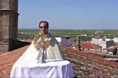 Un párroco se sube a lo más alto del tejado de su parroquia para bendecir a los vecinos