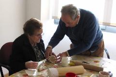 Fermín, voluntario en paliativos, ayudando a una anciana.