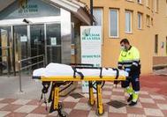 Personal sanitario traslada una camilla a las puertas de la residencia Cáxar de la Vega.