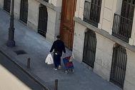 Un hombre camina por el centro de Madrid después de hacer la compra.