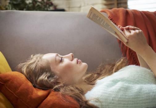 Una mujer leyendo en su casa. Foto: Getty.