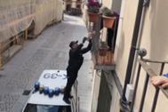 Un agente de Policía, subido sobre el coche patrulla, le hace llegar los pasteles a la vecina de Jaca.